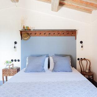 Ispirazione per una camera da letto country con pareti bianche e pavimento multicolore