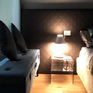 This is an example of a small modern master bedroom in Turin with white walls and light hardwood floors.