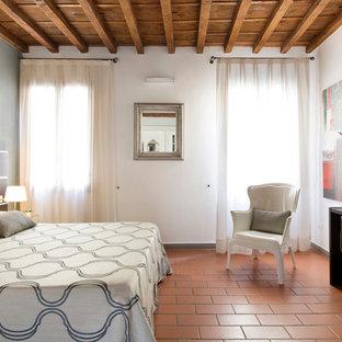 На фото: гостевая спальня среднего размера в современном стиле с белыми стенами, полом из терракотовой плитки и оранжевым полом с
