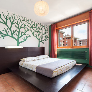 Contemporary master bedroom in Rome with green walls and terra-cotta floors.