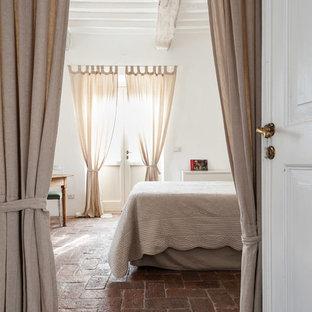 Modelo de dormitorio principal, campestre, con paredes blancas, suelo de ladrillo y suelo rojo