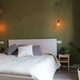 Design ideas for a mid-sized scandinavian master bedroom in Milan with green walls and laminate floors.