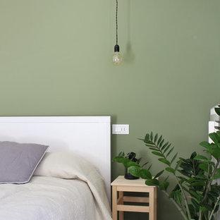 Modelo de dormitorio principal, nórdico, de tamaño medio, con paredes verdes y suelo laminado