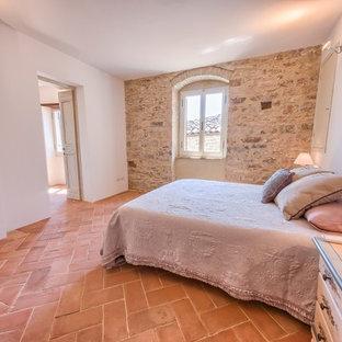 Modelo de dormitorio principal, mediterráneo, de tamaño medio, con paredes blancas y suelo de baldosas de terracota