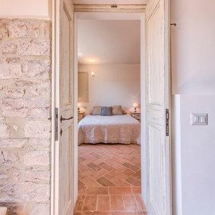 На фото: хозяйская спальня среднего размера в средиземноморском стиле с белыми стенами и полом из терракотовой плитки с