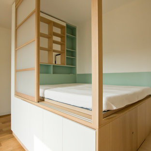 This is an example of a small scandinavian loft-style bedroom in Milan with light hardwood floors and brown floor.