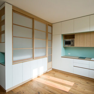 Inspiration for a small scandinavian loft-style bedroom in Milan with light hardwood floors and brown floor.