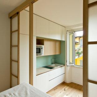 Aménagement d'une petite chambre mansardée ou avec mezzanine scandinave avec un mur blanc, un sol en bois clair et un sol marron.