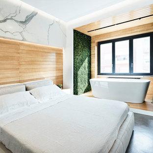 Esempio di una camera matrimoniale minimal di medie dimensioni con pareti bianche, pavimento in cemento, nessun camino e pavimento grigio
