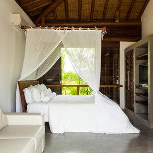 Foto di una camera da letto tropicale con pareti bianche, pavimento in cemento e pavimento grigio