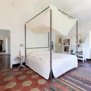 Exempel på ett medelhavsstil huvudsovrum, med vita väggar, betonggolv och flerfärgat golv