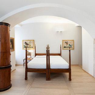 Immagine di una camera matrimoniale mediterranea con pareti bianche, parquet chiaro, stufa a legna e cornice del camino in metallo