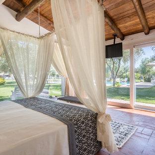 他の地域のトロピカルスタイルのおしゃれな寝室 (テラコッタタイルの床、赤い床)