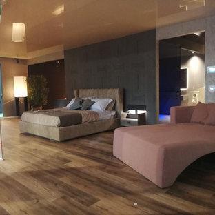 Foto di una grande camera matrimoniale minimalista con pareti grigie, pavimento in vinile, camino ad angolo, cornice del camino in intonaco e pavimento marrone