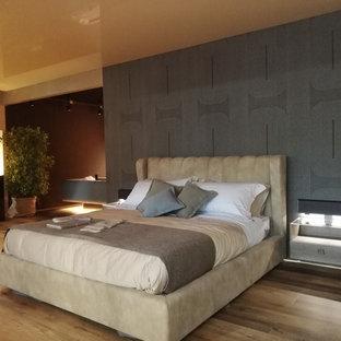 Ispirazione per una grande camera matrimoniale minimalista con pareti marroni, pavimento in vinile, camino ad angolo, cornice del camino in intonaco e pavimento marrone