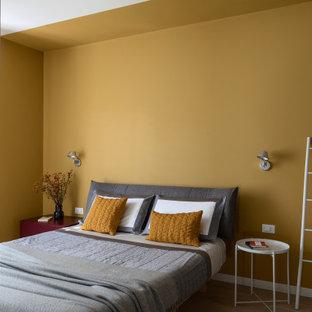 Foto de dormitorio principal, contemporáneo, de tamaño medio, con paredes amarillas y suelo marrón