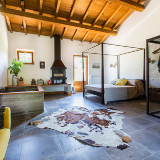 Photo of an expansive industrial master bedroom in Rome with a hanging fireplace, a metal fireplace surround and white walls.