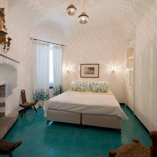 Immagine di una grande camera matrimoniale mediterranea con pareti bianche, pavimento con piastrelle in ceramica, camino classico, cornice del camino in intonaco e pavimento turchese