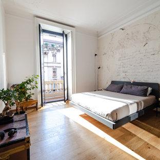 Immagine di una grande camera matrimoniale minimal con pareti bianche, pavimento marrone, pavimento in legno massello medio e carta da parati