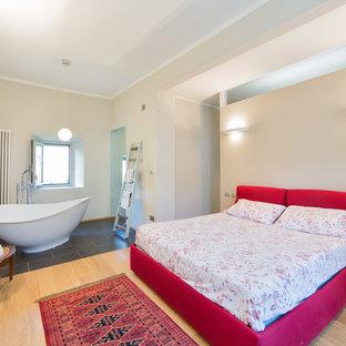 Imagen de dormitorio principal, bohemio, grande, con paredes beige y suelo de madera clara