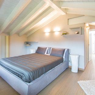 Esempio di una camera da letto contemporanea con pareti beige e parquet chiaro