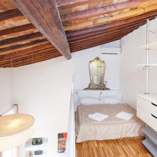 Idee per una camera da letto stile loft design con pareti bianche, pavimento in legno massello medio, pavimento marrone, travi a vista e soffitto a volta