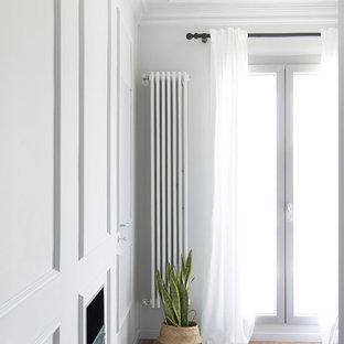 ミラノの中くらいのコンテンポラリースタイルのおしゃれな主寝室 (グレーの壁、無垢フローリング、漆喰の暖炉まわり、茶色い床) のレイアウト