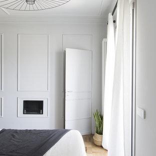 ミラノの中くらいのコンテンポラリースタイルのおしゃれな主寝室 (グレーの壁、無垢フローリング、漆喰の暖炉まわり、茶色い床)