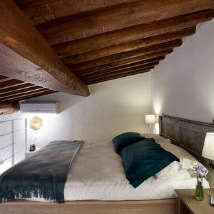Imagen de dormitorio tipo loft, campestre, pequeño, con paredes blancas, suelo de madera clara y suelo beige