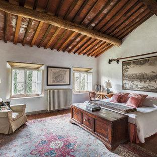 Foto på ett stort lantligt huvudsovrum, med vita väggar, klinkergolv i terrakotta och rött golv