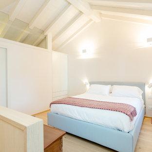 Ispirazione per una camera matrimoniale mediterranea con pareti bianche, parquet chiaro e pavimento beige