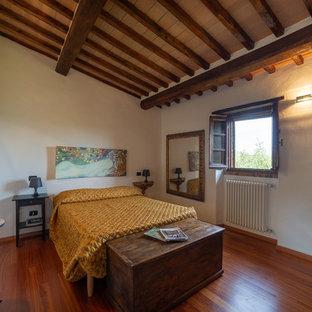 Esempio di una camera da letto country con pareti bianche, pavimento in legno massello medio e pavimento marrone