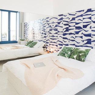 Immagine di una camera matrimoniale mediterranea con pareti bianche, nessun camino e pavimento bianco