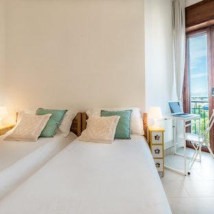 Idee per una camera degli ospiti mediterranea con pareti bianche e pavimento beige