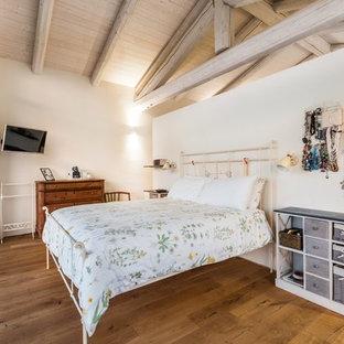 Immagine di una grande camera da letto stile loft in campagna con pareti bianche e pavimento in legno massello medio