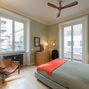 Large midcentury master bedroom in Milan with green walls and painted wood floors.