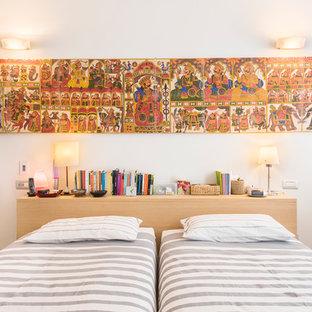 Ispirazione per una camera da letto mediterranea con pareti bianche, pavimento in legno massello medio e pavimento marrone