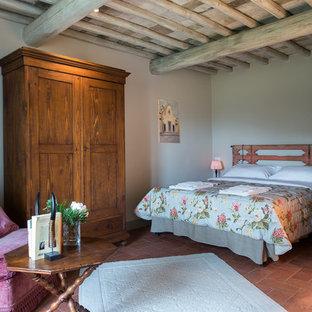 Пример оригинального дизайна: хозяйская спальня в стиле кантри с белыми стенами и полом из терракотовой плитки