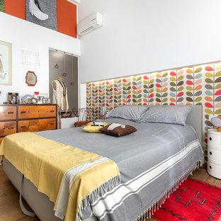Immagine di una grande camera matrimoniale bohémian con pareti bianche e pavimento in legno massello medio