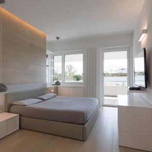 Immagine di una camera da letto minimal con pareti bianche, parquet chiaro e pavimento beige