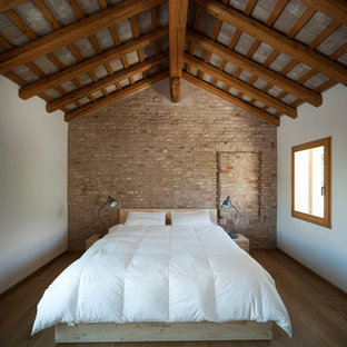 Idéer för ett industriellt huvudsovrum, med vita väggar och ljust trägolv