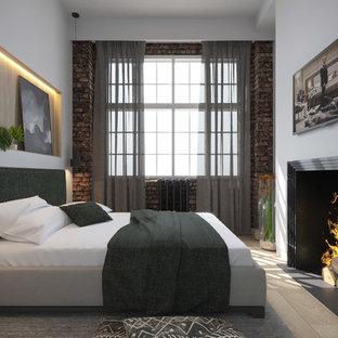 Imagen de dormitorio principal, contemporáneo, pequeño, con paredes grises, suelo de madera en tonos medios, chimenea de doble cara y marco de chimenea de piedra