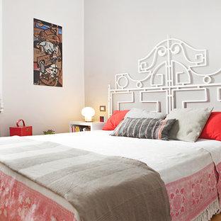 Immagine di una camera matrimoniale minimal con pareti bianche e parquet chiaro
