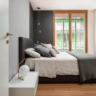 Idee per una camera padronale minimalista di medie dimensioni con pavimento in legno massello medio, pareti grigie e pavimento marrone