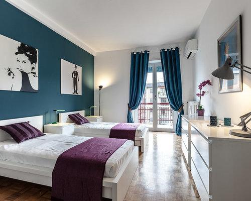 Camera da letto con pavimento in legno massello medio e pareti blu ...