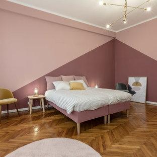 Imagen de dormitorio principal, actual, de tamaño medio, con paredes rosas, suelo marrón y suelo de madera en tonos medios