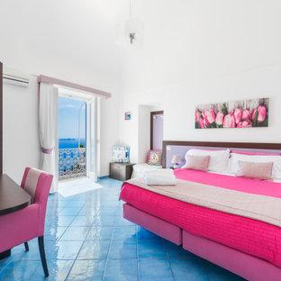 Immagine di una grande camera matrimoniale moderna con pareti bianche, pavimento in gres porcellanato, pavimento turchese e soffitto a volta