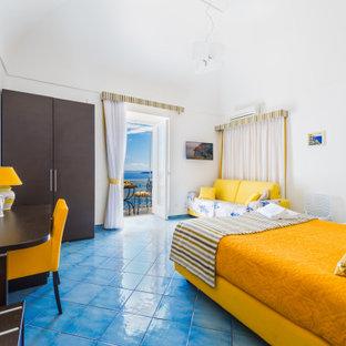 Modelo de dormitorio principal y abovedado, minimalista, grande, con paredes blancas, suelo de baldosas de porcelana y suelo turquesa