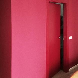 Réalisation d'une petit chambre parentale design avec un mur rouge et un sol en vinyl.