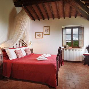 Modelo de dormitorio principal, de estilo de casa de campo, de tamaño medio, con paredes blancas, suelo de baldosas de terracota y suelo naranja